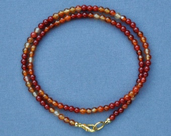 Very delicate princess necklace of small, round natural carnelian beads, small round red treated carnelian beads and gold toggle clasp.