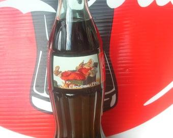 Coca Cola Sundblom Santa Coke Bottle Christmas 1996 / Sealed Bottle features Reclining Santa having a Coca Cola