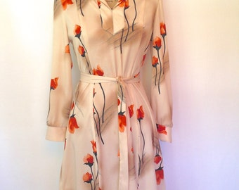Vintage beige dress w/orange black and brown tulip design. Fitted bodice with tie at waist. V-neck with wide lapel. Size Medium