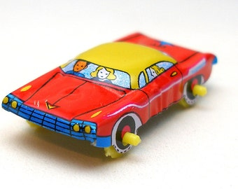 60s tin toy CAR, red with blue & yellow. Made in Japan.