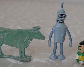Tiny Kokeshi, Tiny Green Lead Cow, and Tiny Bender