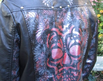 Black vegan leather moto jacket with painted skull and wings design in red and gray. Junior size large.