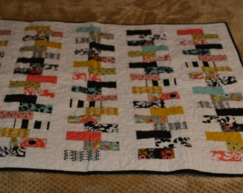 Quilted wall hanging or lap quilt. Machine pieced and quilted in beautiful corals, turquoise, black, white yellow, zipper quilt pattern