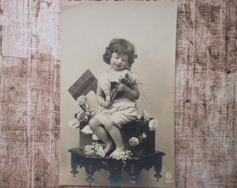 postcard of a sweet girl with some flowers, vintage postcard