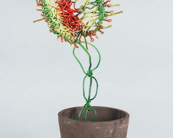 Venus Fly Trap made out of wire, growing out of a potted swamp.