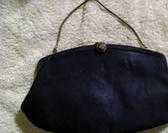 Black clutch bag with chain and needlepoint stitching on clasp