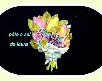 a bouquet of flowers has salt dough hanging has