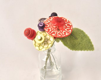 red, purple, and green button flower bottle bouquet