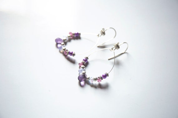 Sterling silver,  with Czech glass  teardrops in purple hues, and glittering rhinestone accents.