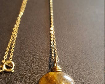 Brown and gold heart shaped gemstone on a gold chain