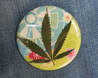 Pressed Cannabis Leaf Button on Yellow & Blue Background