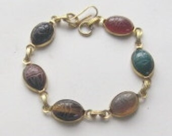 "Bracelet 7.5""L-6 Egyptian Scarabs made of various gemstones , gold tone metal setting and strong clasp. Each scarab has hieroglyphs on back."