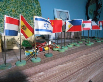 very old world flags on stems in wood base