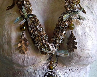 Moss green woven ribbons, yarns, and threads necklace with glass beads, brass charms and green faceted glass pendant statement piece.