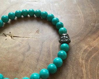 Turquois Buddha 2: an elastic beaded bracelet with a buddha head, rainbow hematite, and turquois