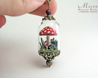Miniature world pendant - A couple of tiny people are resting under a giant fly agaric mushroom amidst giant blades of grass and plants