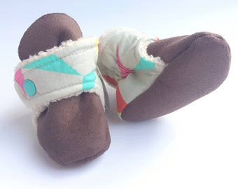 Bright triangles baby booties. Aqua, pink, red and teal on neutral baby booties.
