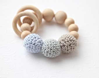 Teething toy with crochet wooden beads and 2 wooden rings. Light grey, pale blue, beige alternately small and big wooden beads rattle.