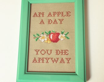 An apple a day you die anyway. Finished and framed cross stitch.