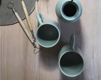 2 white enamel water green stoneware Mugs