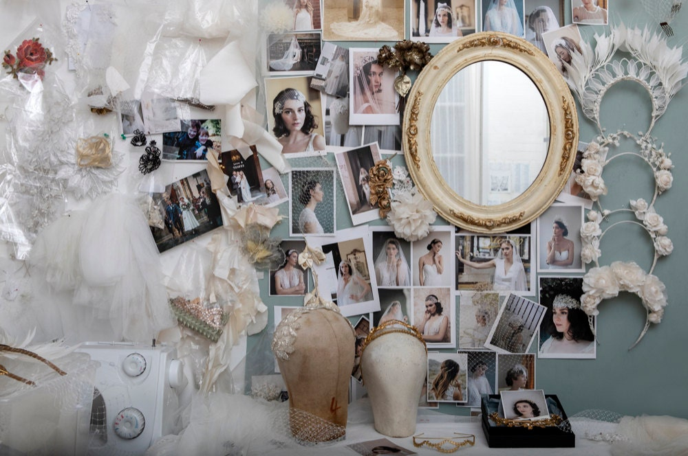 Rae's small London studio space, featuring a desk covered in tulle and tiaras and a wall pinned with model shots and fabric scraps.