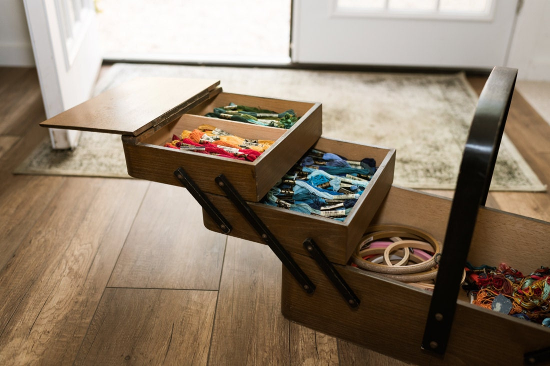 A sewing box filled with embroidery floss, organized by color