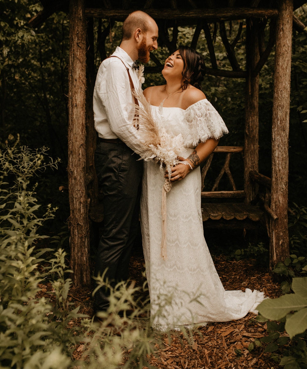 A portrait of Sarah and Chris Schalago in front of a rustic gazebo on their wedding day.