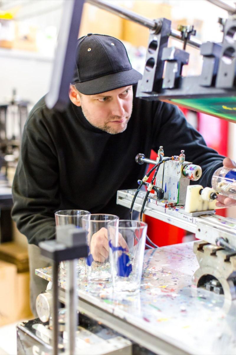 Brett works on printing states onto pint glasses using a glass press.