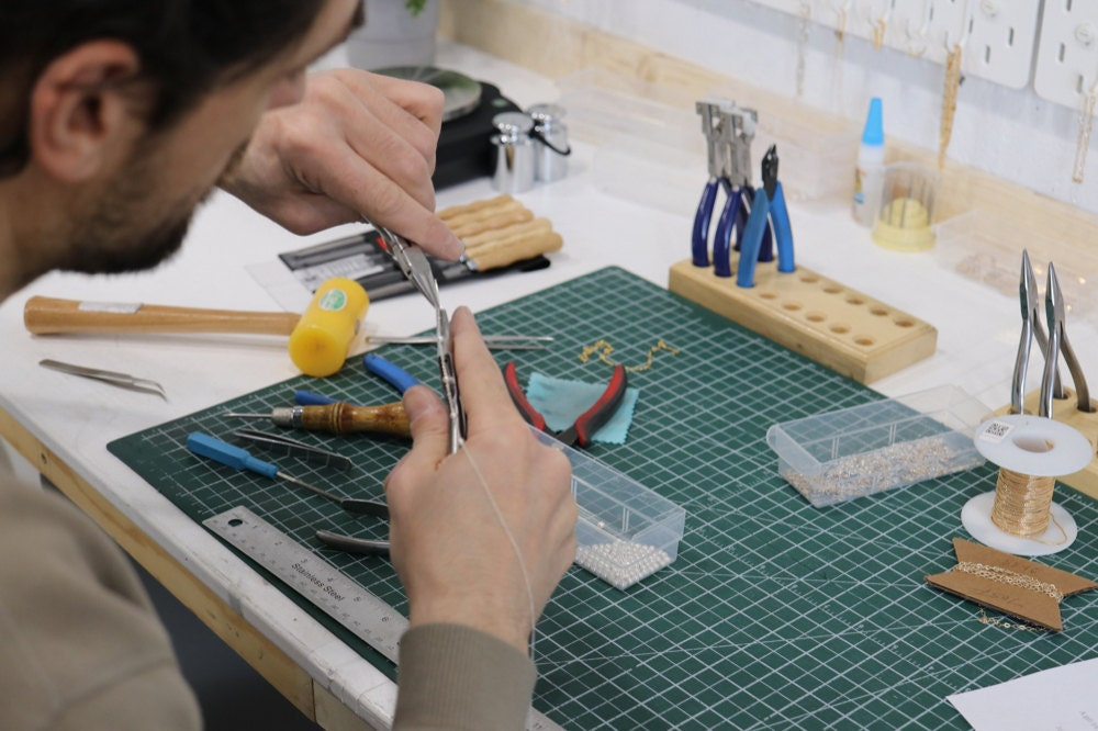 Sabrina's partner uses pliers to assemble a dainty chain at their jeweler's workbench.