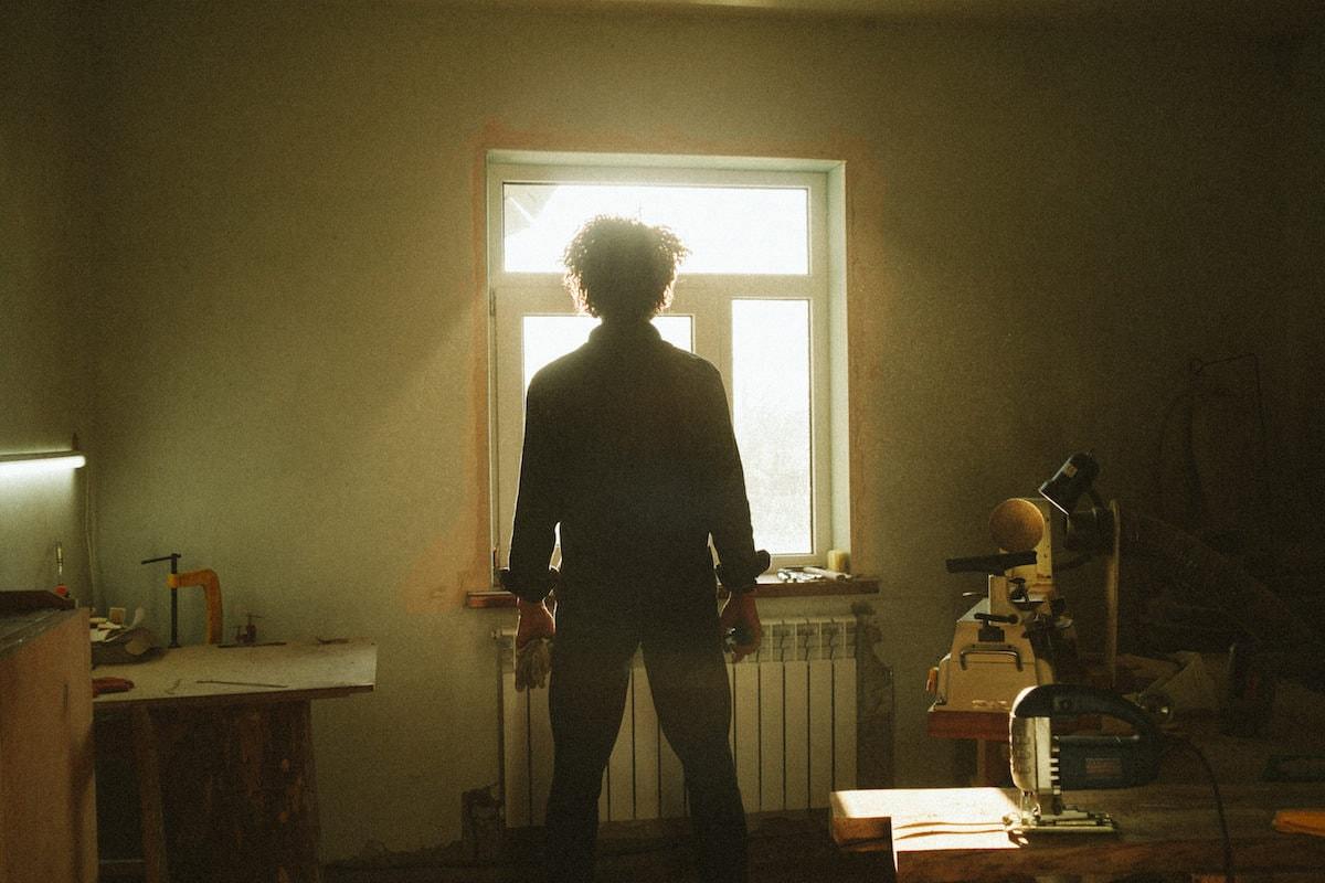 Kirill standing in his studio, looking towards the sunny window