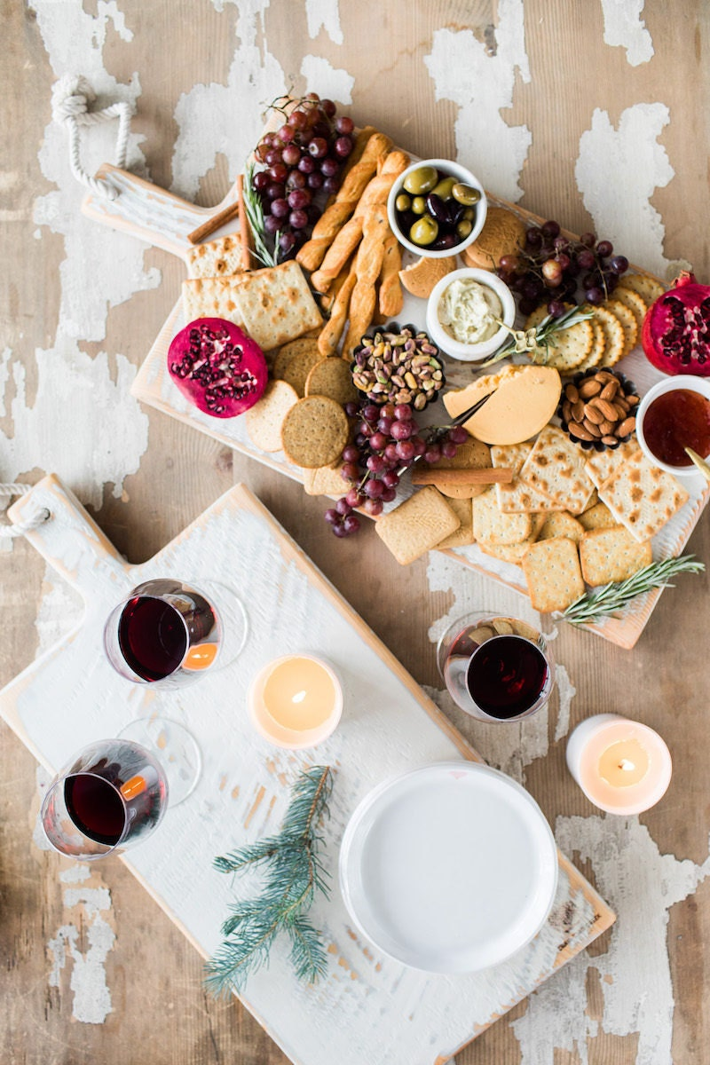Festive holiday charcuterie spread on a rustic white cutting board