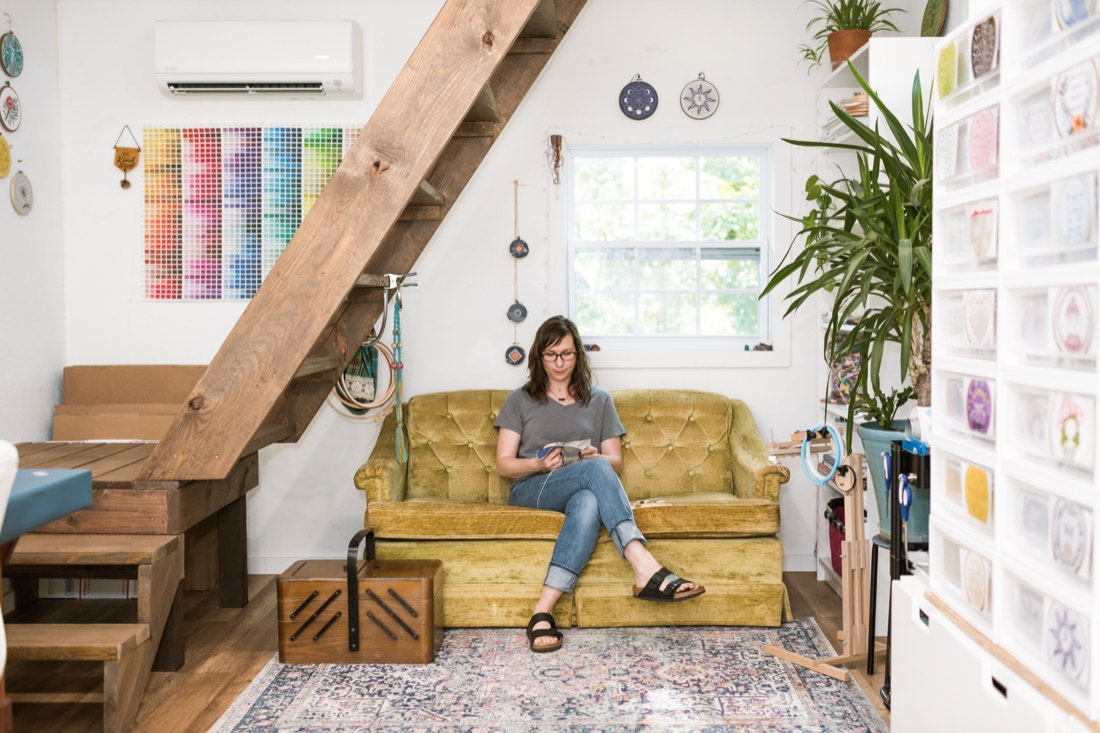 Liz sits on a couch in her cozy studio space and works on some embroidery