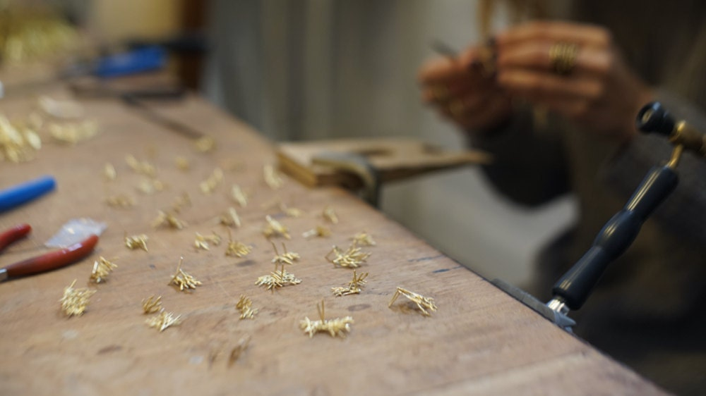A closeup of Maria's hands as she works on assembling rows of botanical post earrings