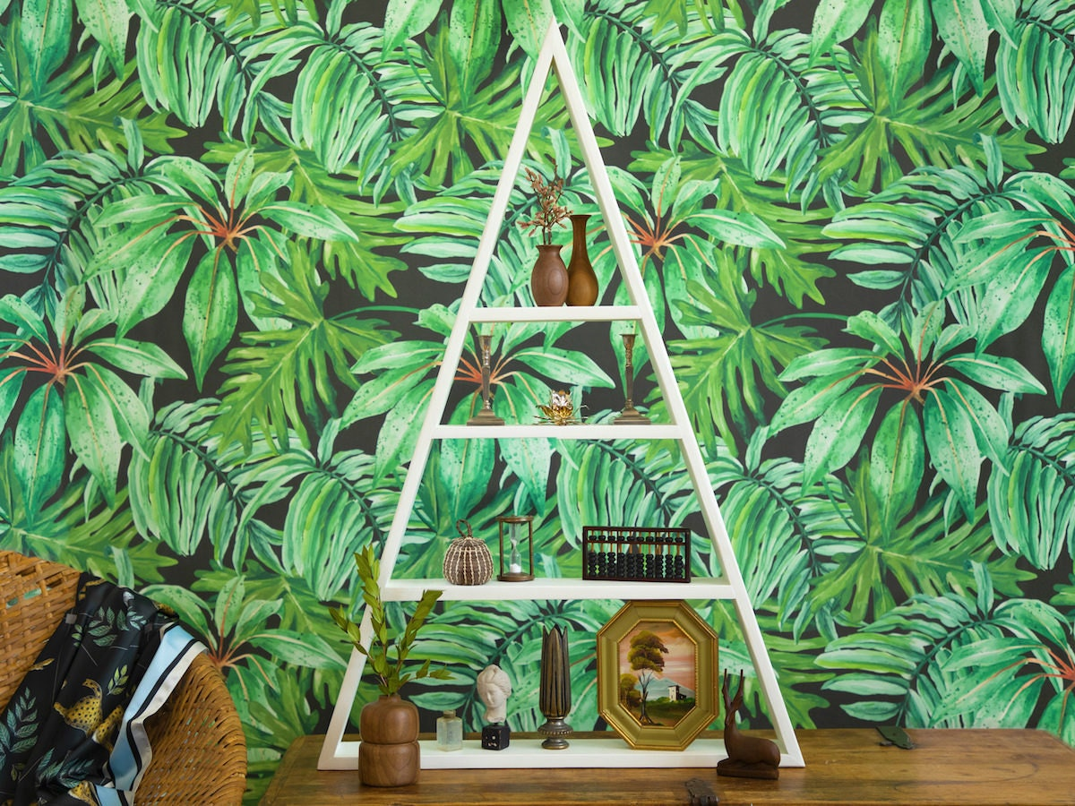 A shelf styled with natural and vintage accents and displayed in front of bold, tropical wallpaper