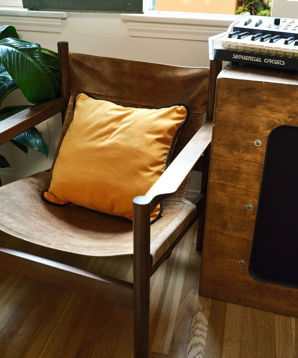A vintage leather slingback chair styled with a mustard-colored velvet throw pillow from Soft Home Textile on Etsy.