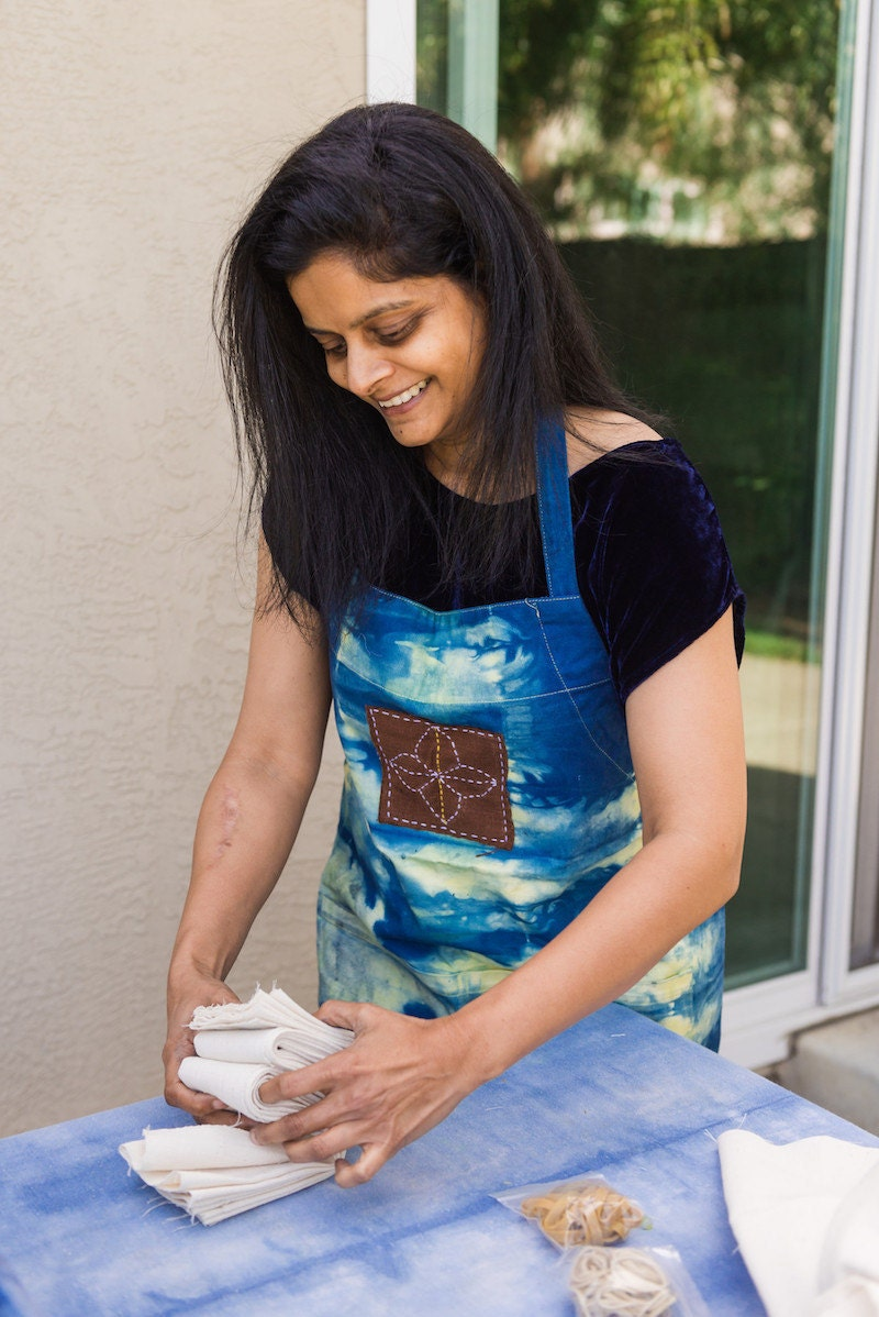 Rajni folds a piece of cotton to prepare it for dyeing