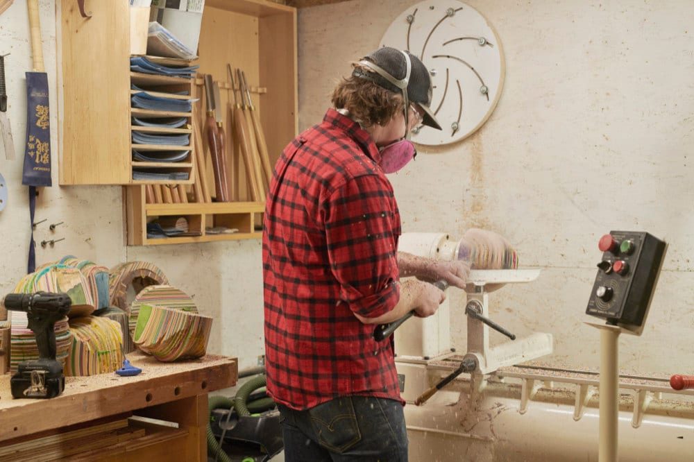 Martinus turns a piece of WIP wood on a lathe.