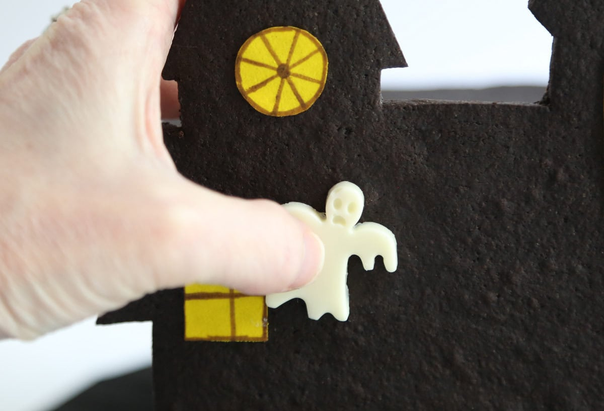 Affixing a candy ghost to the front of the house using melted chocolate.