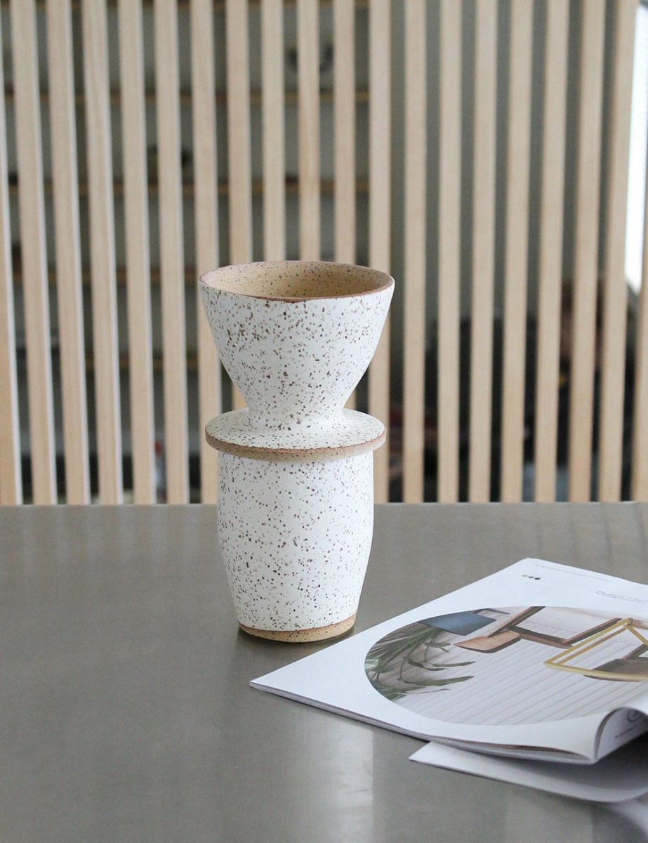 A speckled ceramic cup with a matching pour-over coffee setup on top.