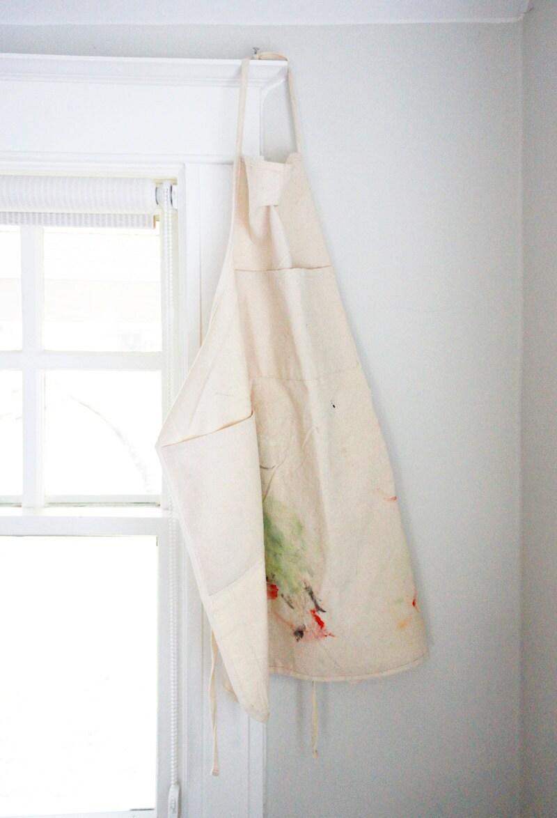 A paint-splattered white apron hangs in Samantha's studio