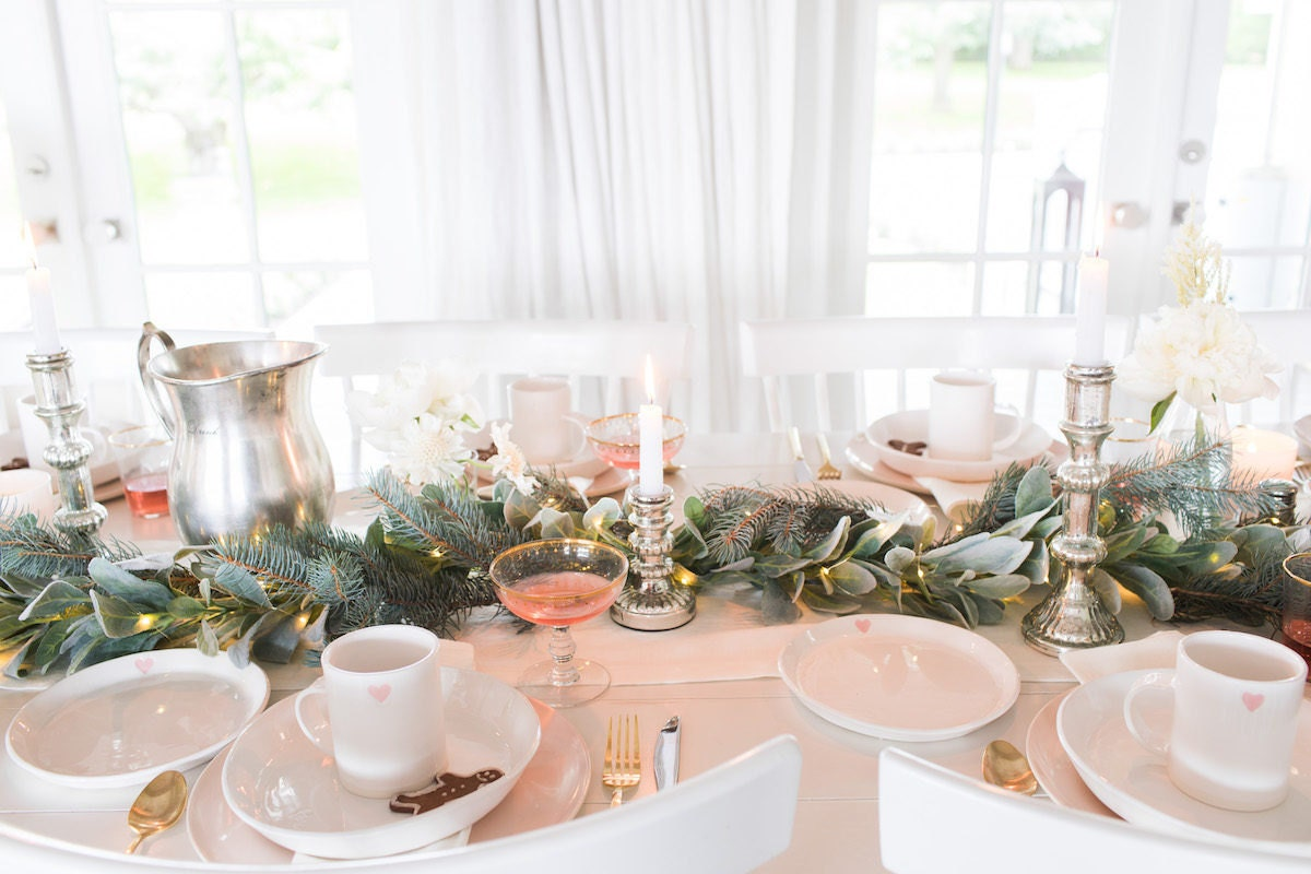 Holiday tabletop with mixed greenery, white ceramic plates, and festive metallic accents