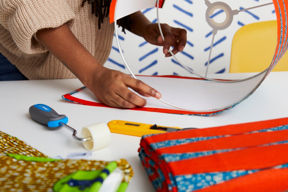 Natalie affixes colorful fabric to a drum-shaped lampshade frame