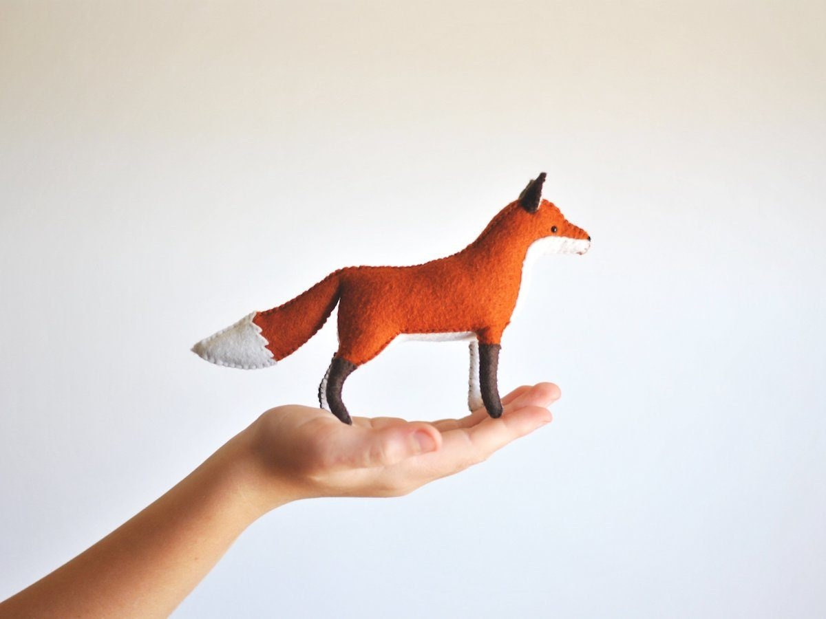 A hand-sewn stuffed felt fox resting in the palm of a person's hand