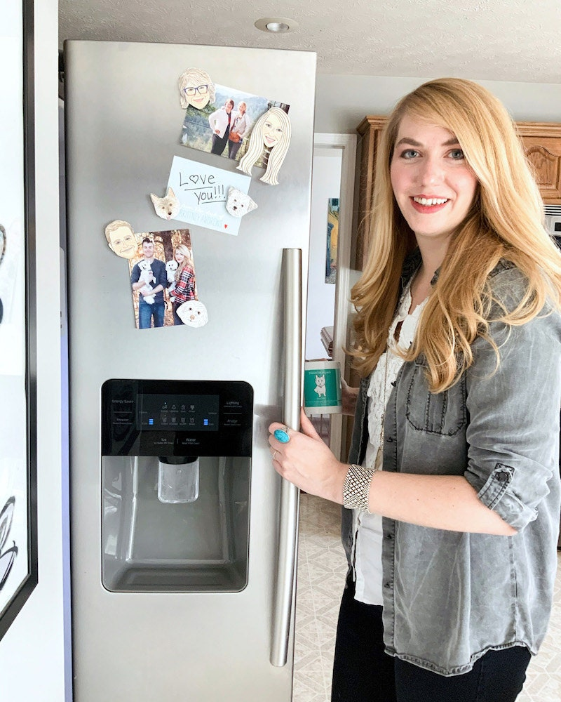 Brittney standing in her kitchen holding her fridge door open with personalized magnets on display