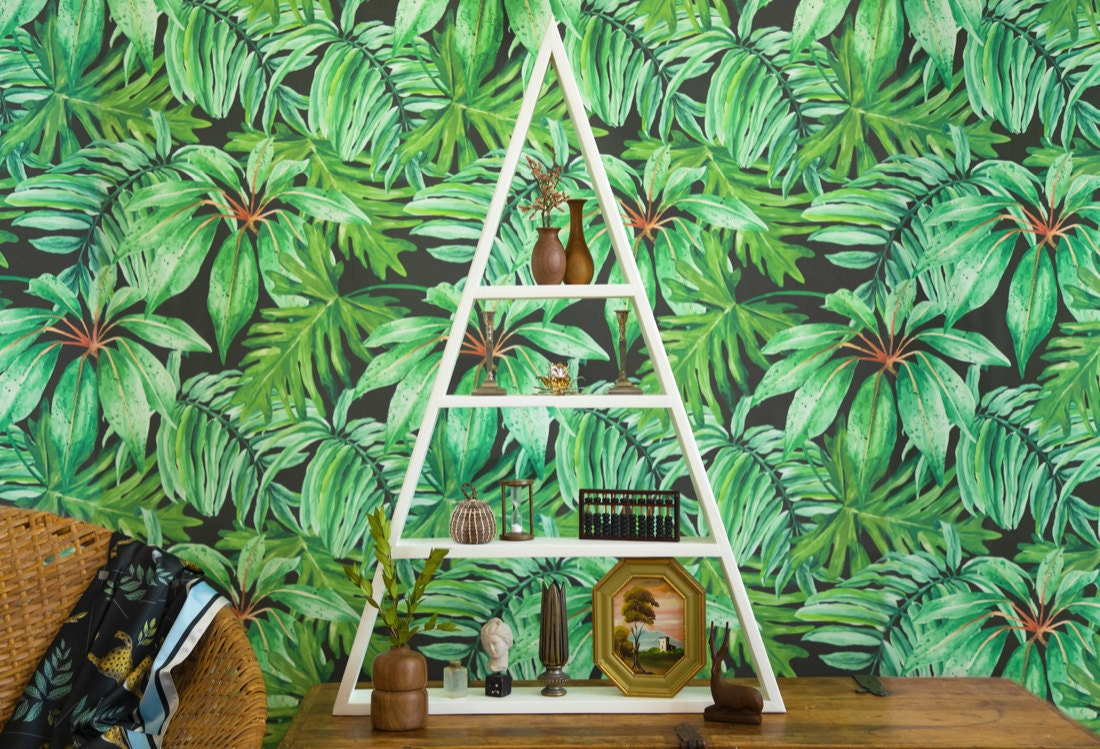 A shelf styled with earthy, natural accents and displayed in front of lush, green, jungle-themed wallpaper.