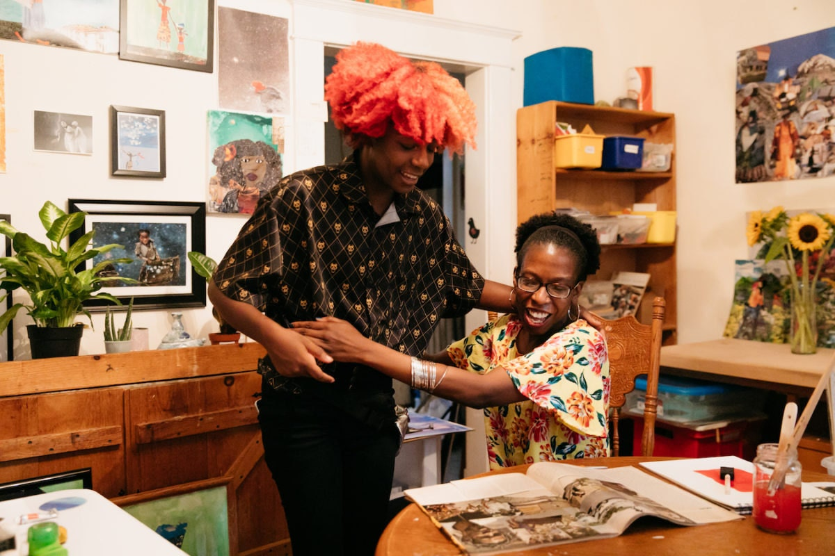 Mirlande embraces her daughter at her dining room table