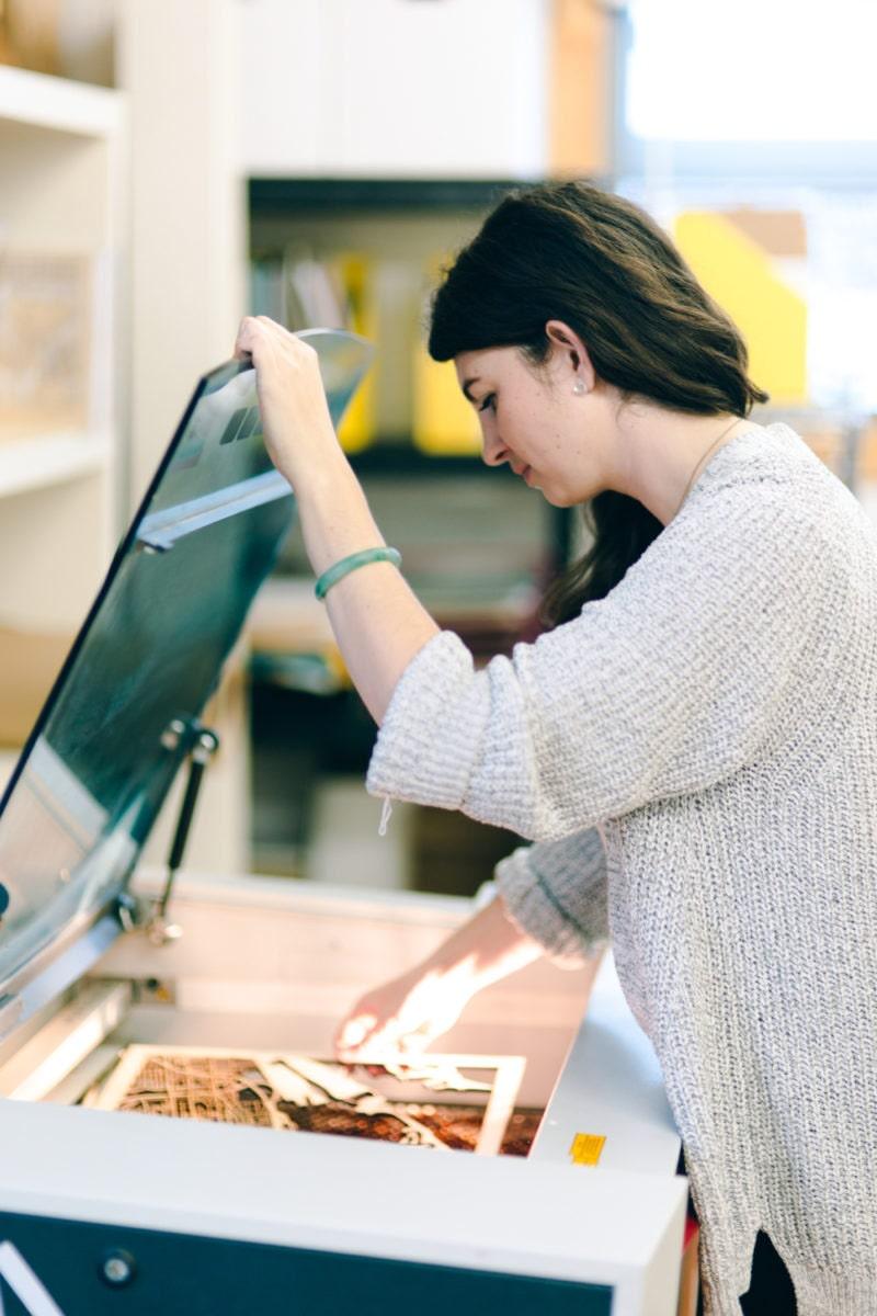 Ali uses her laser cutter in her studio.