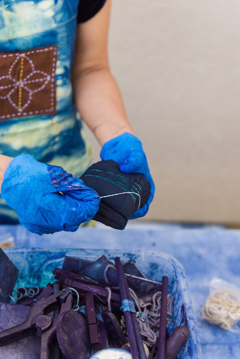 Rajni removes rubber bands from a freshly dyed piece of fabric