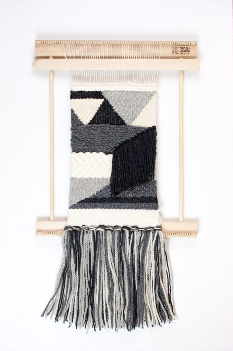 A weaving loom kit displaying a nearly finished piece.