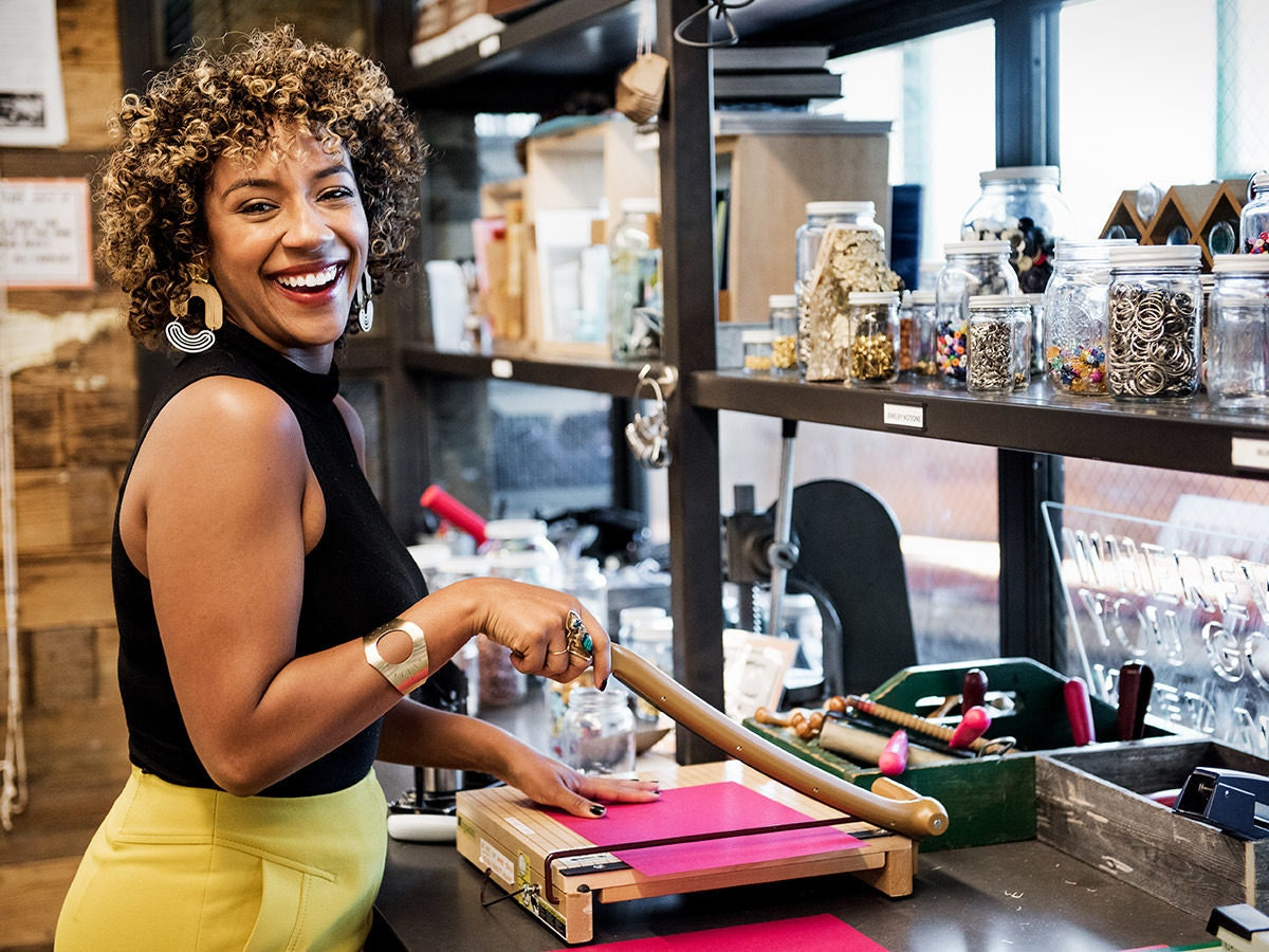 Etsy Trend Expert and Making It judge Dayna Isom Johnson smiles as she cuts paper